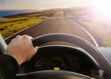 Hands of a driver on steering wheel of a car. And empty asphalt road Royalty Free Stock Photos