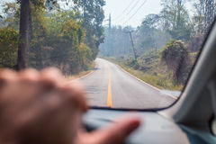 Hands of a driver on steering wheel of a car on the road. In Thailand Royalty Free Stock Images