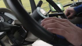 Hands of driver on steering wheel of tractor riding on farm field. Hands of middle aged caucasian driver on big round steering wheel of tractor riding on farm stock video footage
