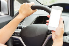 Hands driving and  holding a phone with empty. Someones hands  driving a car and holding a phone with empty  screen Royalty Free Stock Photos