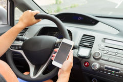 Hands driving and  holding a phone. Someones hands  driving a car and holding a phone Stock Photography