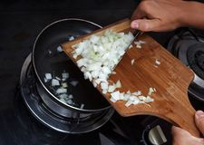 Hands drop chopped onions from board into pan Stock Image