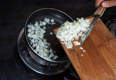 Hands drop chopped onions from board into pan Stock Photography