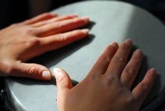 Hands on the drum. Medium sized drum on the laps of performer. Artist's hands are rested on the instrument stock photo