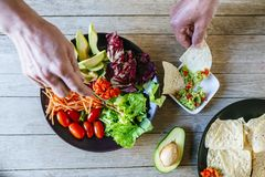 Hands eating avocado salad and plate of nac. Close-up of couple`s hands eating avocado salad and plate of nachos with homemade guacamole Stock Photography