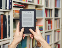 Hands ebook tablet. Hands holding a ebook reading device and books on the background Stock Image