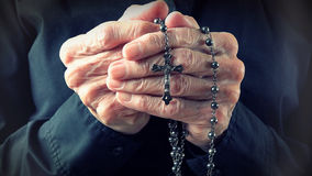 Hands of an elder woman holding a rosary while praying Stock Photos