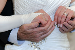 Hands of elderly bride and groom together. Stock Photography