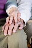 Hands of elderly couple touching on knee. Hands of affectionate elderly couple touching on knee Royalty Free Stock Photo