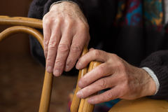 Hands of an elderly man. Two hands of an elderly man lying on the back of a chair Royalty Free Stock Image