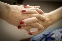 Hands of elderly person with senile dementia. Hands of old woman and elderly caregiver stock image