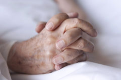 Hands. Of an elderly resting on the bed Stock Photos