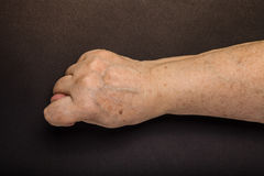 Hands of elderly woman on black background. Toned royalty free stock photography