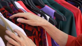 Hands of elderly woman choosing clothes in fashion shop while shopping. Close up mature woman shopping clothes in stylish shop stock footage