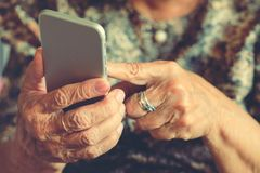 Hands of an elderly woman holding a mobile phone. In vintage style stock image
