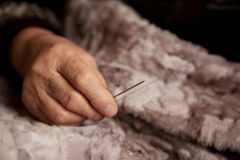 Hands of an elderly woman for sewing Stock Images