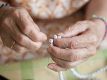 Hands of elderly woman threading a necklace Stock Photo