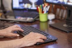 Hands of an elderly woman typing on a pc keyboard stock photos