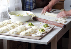 Hands of the elderly woman unroll dough for pies on a dish Royalty Free Stock Photo