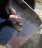 Hands of the elderly woman washing. In the old wooden board Stock Image