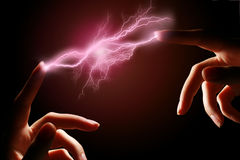 Hands and electric discharge. Hands and electric discharge over black background royalty free stock image