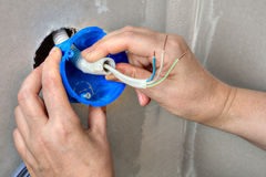 Hands electrician fix electricity round plastic outlet box on wa Stock Photo