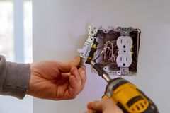 The hands of an electrician installing a power switch. To the electrical junction box electricity screwdriver wall installation house work industry worker stock image
