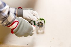 Hands of electrician installing socket in gypsum wall stock photography