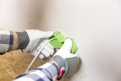 Hands of electrician installing socket in gypsum wall stock photo