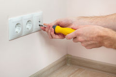 The hands of an electrician installing a wall power socket. The hands of an electrician installing a wall power socket Stock Photo