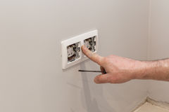 The hands of an electrician installing a wall power socket. Stock Photography