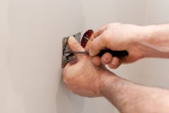 The hands of an electrician installing a wall power socket Royalty Free Stock Images