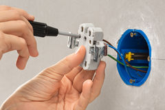 Hands of electrician with screwdriver installing light switch Stock Photography