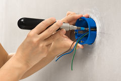 Hands of electrician with screwdriver installing plastic outlet stock photo