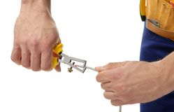 Hands of electrician stripping end of wire Royalty Free Stock Photography