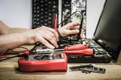 Hands of electronic engineer repairing broken laptop. Hands of electronic engineer probing parts of broken laptop with multimeter gauge. Side view royalty free stock photos