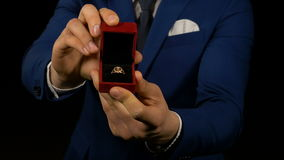 Hands of an elegant man holding and presenting jewelry box with ring inside. Hands of elegant man holding and presenting jewelry box with ring inside stock footage