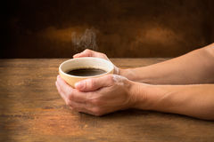 Hands embracing hot cup of coffee Stock Photography