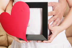 Hands embracing a pregnant woman belly with her hands holding a Royalty Free Stock Photo