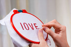Hands embroidering a word love Stock Photos