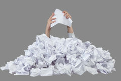 Hands with empty crushed paper reaches out from big heap of crumpled papers. Isolated on gray backround Stock Photo