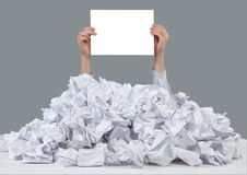Hands with empty paper reaches out from big heap of crumpled papers Royalty Free Stock Images