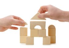 The hands establishes a toy roof on wooden cubes Royalty Free Stock Photos