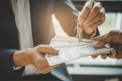 Hands of estate agent giving keys to the customer and bank note Royalty Free Stock Images