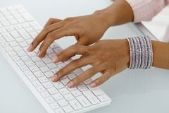 Hands of ethnic businesswoman typing Royalty Free Stock Photo