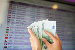 Hands with euro money over currency exchange rates Stock Photos