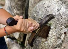 HANDS and excalibur sword in the stone. Excalibur the famous sword in the stone of king Arthur in the forest Stock Photo