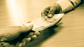 Hands exchanging money. Sepia image of a businessman handing over a stack of fifty Euro bills to a female hand over a pine desk stock photo