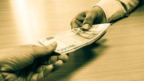 Hands exchanging money stock photo