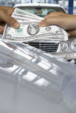 Hands exchanging one hundred dollar bills over luxury cars Royalty Free Stock Photo